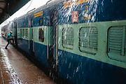 A man leaps into a train as the monsoon rain splashes onto the railway platform, Chhatrapati Shivaji Terminus (CST), Mumbai, India