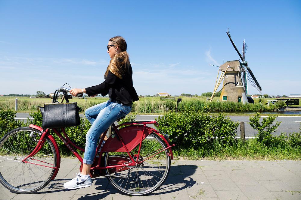 Bij Oegstgeest rijdt een meisje op een stadsfiets langs een windmolen.<br /> <br /> Near Oegstgeest a girl cycles on a city bike near a wind mill