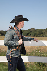 rugged good looking cowboy by a fence on a ranch