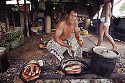 His 10-year-old daughter walks by as Alatupe Alatupe cooks sausages in the family cooking shed behind the main house for part of the White Sunday feast. The Lagavale family lives in a 720-square-foot tin-roofed open-air house with a detached cookhouse in Poutasi Village, Western Samoa. The Lagavales have pigs, chickens, a few calves, fruit trees and a vegetable garden. Material World Project.