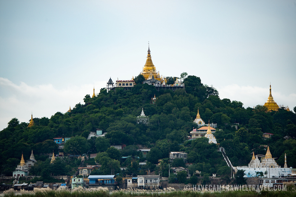 The gold covered umbrella of on the many temples in the hills of Sagaing, near Mandalay, as seen from across the Ayeyarwaddy River.