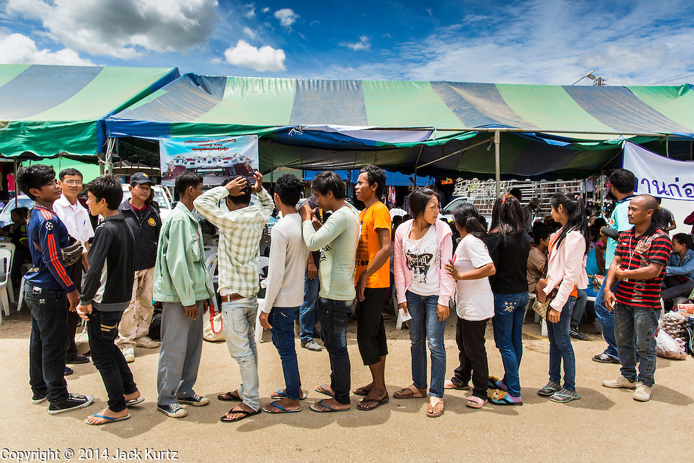 09 JULY 2014 - ARANYAPRATHET, SA KAEO, THAILAND: Cambodian migrant workers line up at the Thai Immigration One Stop Service Center in Aranyaprathet on the Thai-Cambodian border. More than 200,000 Cambodian migrant workers, most undocumented, fled Thailand in early June fearing a crackdown by Thai authorities after a coup unseated the elected government. Employers have been unable to fill the vacancies created by the Cambodian exodus and the Thai government has allowed them to return. The Cambodian workers have to have a job and their employers have to vouch for them. The Thai government is issuing temporary ID cards to allow them to travel openly to their jobs. About 800 Cambodian workers came back to Thailand through the Aranyaprathet border crossing Wednesday. The Thai government has opening similar service centers at three other crossing points on the Thai-Cambodian border.    PHOTO BY JACK KURTZ