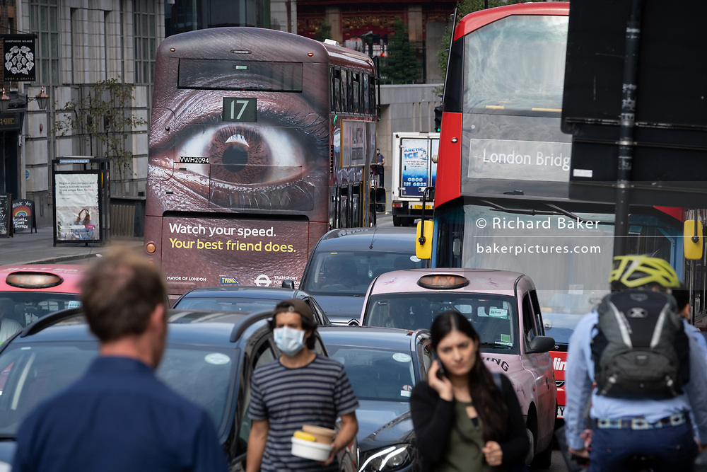 Pedestrians and busy traffic on the Farringdon Road in the City of London with a London bus carrying an ad about speeding in the capital, on 16th September 2020, in London, England.