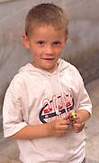 Boy age 5 on sidewalk holding toy.  Torun Poland
