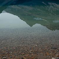 Mount Thompson & Portal Peak reflect in Bow Lake in Banff National Park, Alberta, Canada.