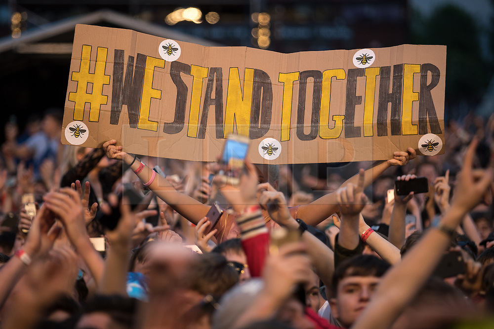 """© Licensed to London News Pictures . 27/05/2017 . Manchester , UK . A woman holds up a hand painted sign , with Manchester bee stickers , reading """" WE STAND TOGETHER """" during the Courteeners' set . Manchester music line up , featuring Courteeners , Charlatans , Blossoms and Cabbage , at the Emirates Old Trafford Stadium . Photo credit : Joel Goodman/LNP"""