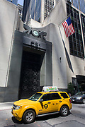 A hybrid Ford Escape Hybrid taxi cab passes the tall doorway of the East River Savings Bank in Lower Manhattan, New York City. Stopped at a red light before continuing its silent journey across the city. The City Council passed a bill in 2003 requiring the New York City Taxi and Limousine Commission to set aside a proportion of new taxi medallions to be granted to vehicles that use cleaner fuels. By uly 2011, New York City had 4,980 hybrid taxis, representing almost 38% of the city's overall fleet,[20] and about 6,000 by September 2012, representing 45% of the taxis in service.