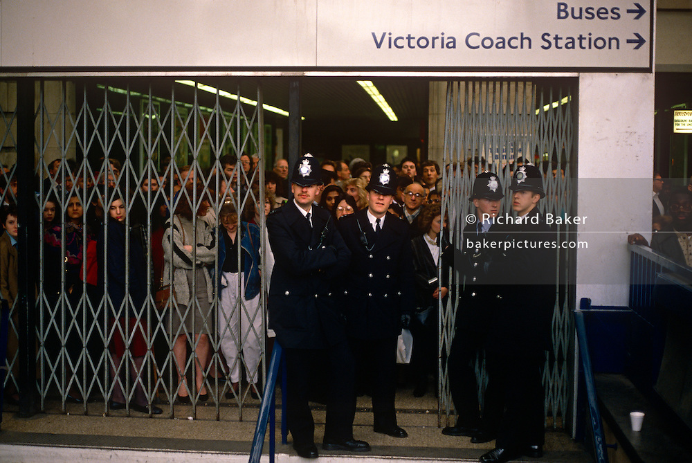 Metropolitan police officers stand guarding a closed underground tube entrance at London's Victoria station. There is a tube strike and capacity is vastly reduced so numbers are being strictly restricted while the tube unions ask drivers and staff not to report for duty. Passengers queue patiently behind the barriers, their faces seen with resigned expressions, as Londoners are typically want to do.