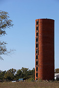 This image is of an abandoned farm silo. Used to store feed in the winter months for livestock when farming was a much simpler buisiness than is is today. In this photo, the roof is no longer atop the structure but the bricks are still intack. The silo stands as a riminder of times past.
