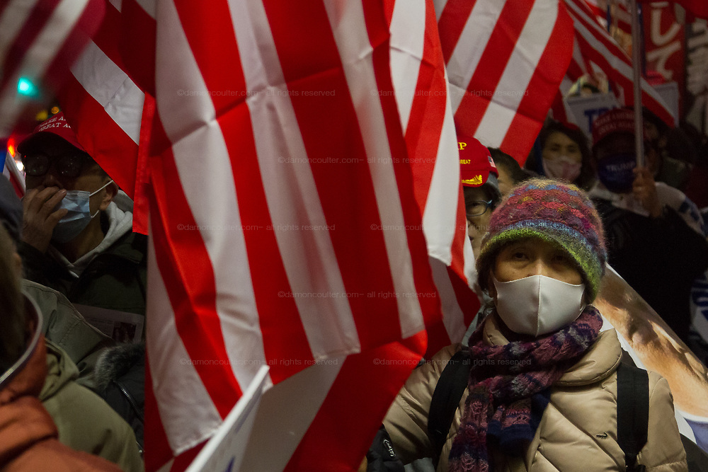 """A Japanese woman, holds, wearing a face mask against COVID-19, holds an American flag  as several hundred people, taking part in a """"March For Trump"""" rally  in support of the out-going United States President, Donald Trump. Tokyo, Japan. Wednesday January 6th 2021. The rally of mostly Japanese people took place as part of a similar rally by Trump-supporters in Washington DC as the results of the 2020 US Presidential election were confirmed."""