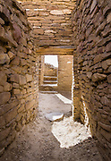 Inside an ancient passage. Pueblo Bonito is a monumental public building (Puebloan Great House) occupied from around 828 to 1126 AD, now preserved at Chaco Culture National Historical Park, New Mexico, USA. The huge D-shaped complex of Pueblo Bonito enclosed two plazas with dozens of ceremonial kivas, plus 600 rooms towering 4 and 5 stories above the valley floor. The functions of this building included ceremony, administration, trading, storage, hospitality, communications, astronomy, and burial, but few living quarters. Chaco Culture NHP hosts the densest and most exceptional concentration of pueblos in the American Southwest and is a UNESCO World Heritage Site, located in remote northwestern New Mexico, between Albuquerque and Farmington. From 850 AD to 1250 AD, Chaco Canyon advanced then declined as a major center of culture for the Ancient Pueblo Peoples. Chacoans quarried sandstone blocks and hauled timber from great distances, assembling fifteen major complexes that remained the largest buildings in North America until the 1800s. Climate change may have led to its abandonment, beginning with a 50-year drought starting in 1130.