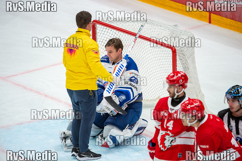 LAUSANNE, SWITZERLAND - OCTOBER 01: Goalie Lukas Flueler #30 of ZSC Lions gets checked by doctor during the Swiss National League game between Lausanne HC and ZSC Lions at Vaudoise Arena on October 1, 2021 in Lausanne, Switzerland. (Photo by Robert Hradil/RvS.Media)