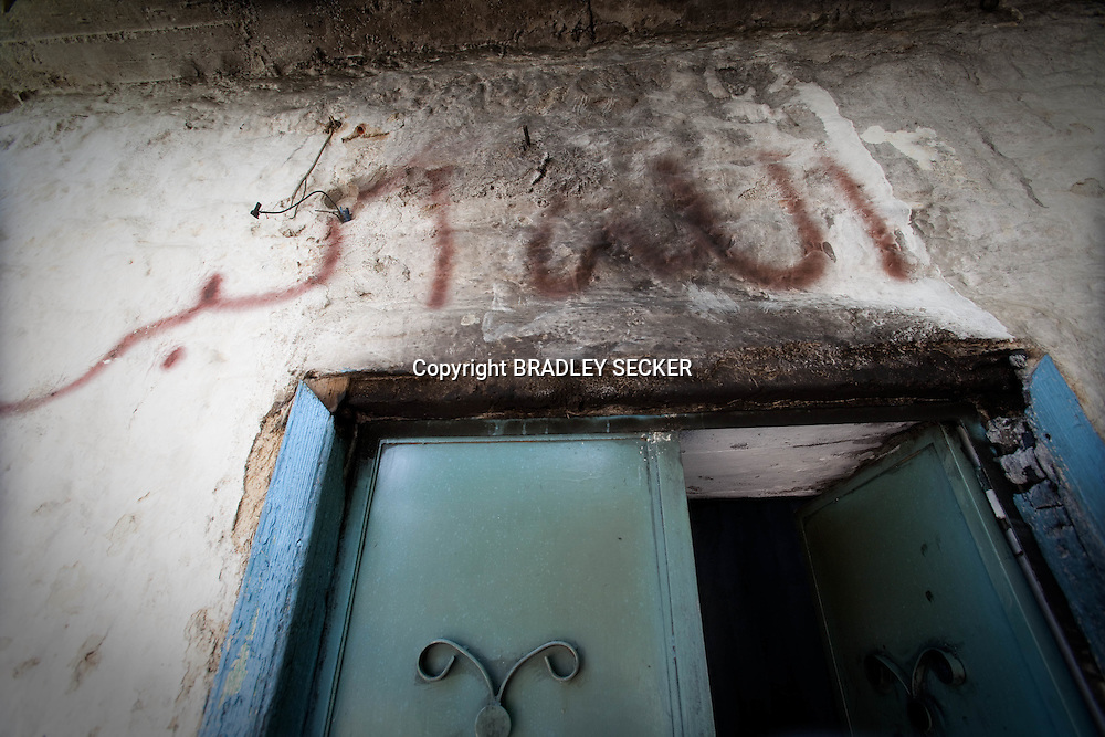 Above the door of a home burnt in a recent attack by the Syrian military, several days previously, is written 'AllahuAkbar' (God is great). Lejj, Idlib province, Syria. 16/06/2012