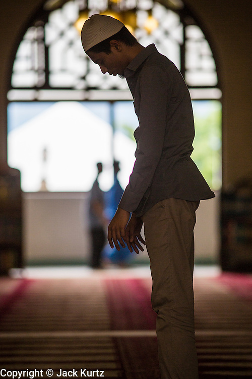 22 DECEMBER 2012 - SINGAPORE, SINGAPORE:  A man prays in the main prayer hall at the Sultan Mosque in Singapore. The Sultan Mosque is the focal point of the historic Kampong Glam area of Singapore. Also known as Masjid Sultan, it was named for Sultan Hussein Shah. The mosque was originally built in the 1820s. The original structure was demolished in 1924 to make way for the current building, which was completed in 1928. The mosque holds great significance for the Muslim community, and is considered the national mosque of Singapore. It was designated a national monument in 1975.           PHOTO BY JACK KURTZ