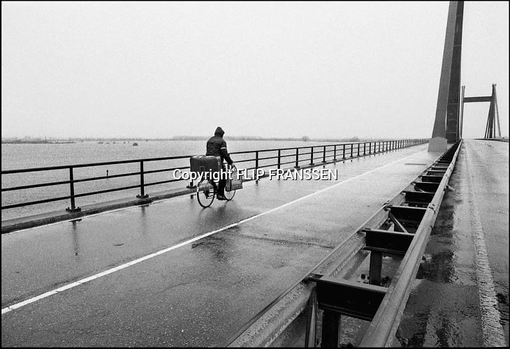 Nederland, Leeuwen, 01-02-1995Eind januari, begin februari 1995 steeg het water van de Rijn, Maas en Waal tot record hoogte van 16,64 m. bij Lobith. Een evacuatie van 250.000 mensen was noodzakelijk vanwege het gevaar voor dijkdoorbraak en overstroming. op verschillende zwakke punten werd geprobeerd de dijken te versterken met zandzakken. Hier verlaat een man op de fiets met slechts een koffer en een tas het gebied richting wijk bij duurstede.Late January, early February 1995 increased the water of the Rhine, Maas and Waal to a record high of 16.64 meters at Lobith. An evacuation of 250,000 people was needed because of flood risk. At several points people tried to reinforce the dikes with sandbags. Foto: Flip Franssen/Hollandse Hoogte