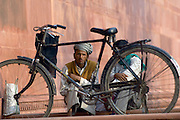 Local men with bicycle sit outside entrance to the Taj Mahal at Agra, Uttar Pradesh, India