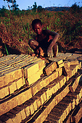 A child piles bricks in in a stack as part of his job in a brick factory, Ruyigi, Burundi