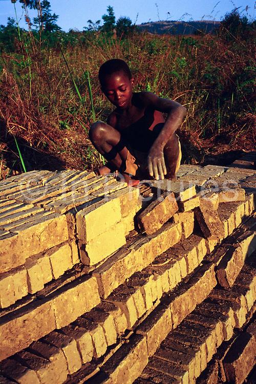 A child piles bricks in in a stack as part of his job in a brick factory, Ruyigi, Burundi