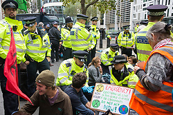 London, UK. 8 October, 2019. Metropolitan Police officers prepare to arrest climate activists from Extinction Rebellion blocking Marsham Street outside the Home Office on the second day of International Rebellion protests to demand a government declaration of a climate and ecological emergency, a commitment to halting biodiversity loss and net zero carbon emissions by 2025 and for the government to create and be led by the decisions of a Citizens' Assembly on climate and ecological justice.
