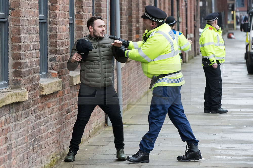 © Licensed to London News Pictures . 07/04/2018. Manchester, UK. Police detain a man as they move to contain fans running through streets and chanting Manchester City slogans in Manchester's Northern Quarter , ahead of the Manchester City vs Manchester United derby match. If they win the match, Manchester City will win the League title. Photo credit : Joel Goodman/LNP