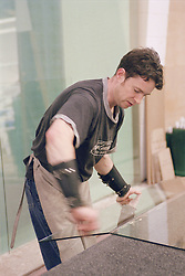 Man working in glass factory lifting piece of glass,