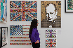 © Licensed to London News Pictures. 21/10/2020. LONDON, UK. A staff member poses with works by artist Gary Hogben, all made from postage stamps. Preview of STARTnet Art Fair at the Saatchi Gallery in Chelsea.  The contemporary art fair showcases local London, as well as international, galleries and individual artists from all over the world.  The fair runs 21 to 25 October with Covid-19 protocols in place for visitors.   Photo credit: Stephen Chung/LNP