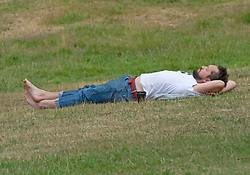 ©Licensed to London News Pictures 14/07/2020     <br /> Greenwich, UK. A man relaxing in Greenwich park, London this afternoon. The sunshine will be making a comeback this weekend but the rest of the week like today will be cloudy. Photo credit: Grant Falvey/LNP