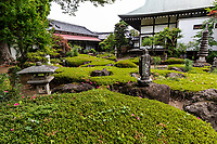 """Shosenji Temple was made by Ogawa Kuro, who developed Ogawa Village along Ome Kaido Road in the Edo period.  The waterway stream of Tamagawajosui that has been used as the water of the village life is part of the temple in the form of a small pond.. The garden is known as """"The Village of Runaway Water"""".  In this unique garden, shrubs have been sculpted around massive stones throughout the garden, with stone pagodas and 33 Kannon statues.  Although the temple grounds and garden are not well maintained, nevertheless,  it is one of the most unique Japanese gardens in the Tokyo area and well worth visiting, especially in spring when azaleas are in bloom.  The weeds and tasteless sculptures need to be overlooked, but the original garden masterful design is its high point.   The temple itself was destroyed in 1819 and again in 1898 but was rebuilt both times.  The temple structures were remodeled in 1916 and again in 1999."""
