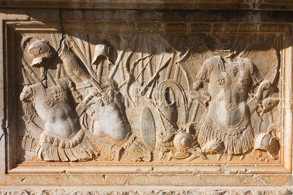 Carvings of battle and heroism outside the Palacio de Carlos V at Alhambra, Granada, Spain. The armour of soldiers of the renaissance period can be seen in readiness for warfare against the foes of the time. The Palace is a Renacentist construction in Granada, southern Spain, located on the top of the hill of the Assabica, inside the Nasrid fortification of the Alhambra. It was commanded by Charles V, Holy Roman Emperor, who wished to establish his residence close to the Alhambra palaces.