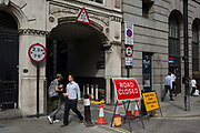 Pedestrians walk past a Road Closed sign at the entrance of Austin Friars in Threadneedle Street in the City of London - the capitals financial district, on 3rd September 2018, in London England. Austin Friars, London was an Augustinian friary in the City of London from its foundation, probably in the 1260s, until its dissolution in November 1538. It covered an area of about 5.5 acres 2.2 hectares a short distance to the north-east of the modern Bank of England and had a resident population of about 60 friars. Nowadays the site is mainly occupied by office blocks.