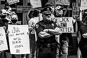 Watsontown, PA (June 28, 2020) -- Watsontown Borough Police Chief Rodney Witherite stands between Black Lives Matter protesters and a group of counter protesters across the street.
