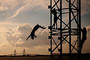 Evan Johnson backflips off the coast guard tower near Pitt Street Bridge in Mt. Pleasant, South Carolina on Monday, June 21, 2021.