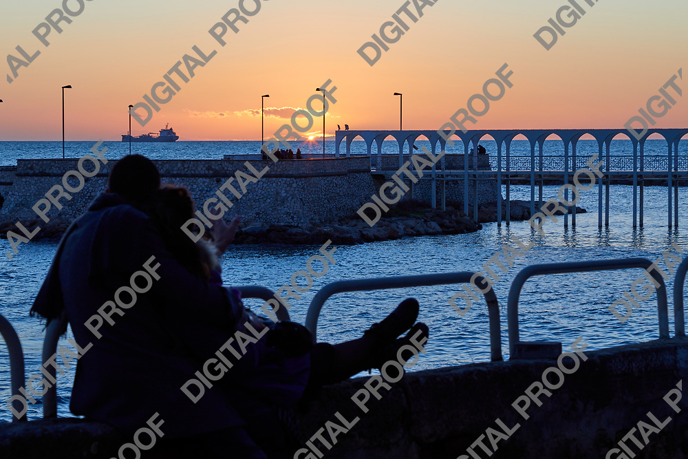 Romantic couple watch the sunset together in a winter afternoon