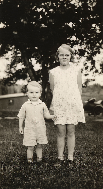 Sister and brother standing next to each other.