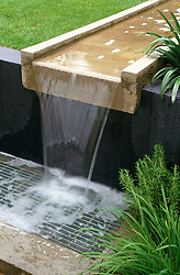 Cascading concrete rill water feature. Protective metal grille.