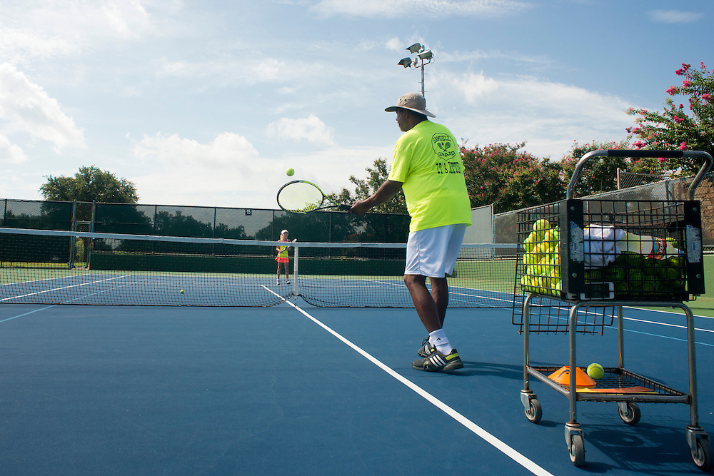 Duey Evans, Director of Tennis at the Samuell Grand Tennis Center, works with Harper Santos, 9, during a private lesson at the Samuell Grand Tennis Center in Dallas, Texas on August 19, 2014. (Cooper Neill for The New York Times)