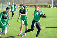 Joe Newell (#11) of Hibernian FC (centre) is all smiles, as he chases Paul McGinn (#6) of Hibernian FC and Kevin Nisbet (#15) of Hibernian FC during the training session for Hibernian FC at the Hibs Training Centre, Ormiston, Scotland on 26 February 2021, ahead of the SPFL Premiership match against Motherwell.