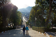 Couple walking down some steps in the evening twlight, mountains in the background, street scene, San Cristobal de las Casas, Chiapas, Mexico.