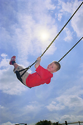 Young boy swinging on playground swing smiling,