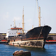 A rusty fishing vessel docked in a harbor near Naples, Italy.