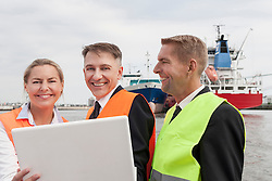 Portrait of business people working on laptop at harbour, Hamburg, Germany