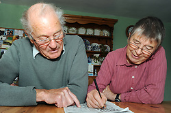 A retired couple enjoy their leisure time doing the crossword together,Cumbria.  Model Released.