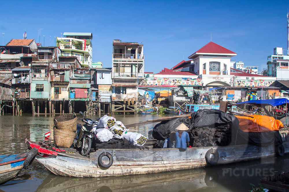 A barge loaded with goods sails on a canal in My Tho, Vietnam, Southeast Asia