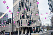 Beneath a high-rise of residential apartments, pink spherical lanterns hang from cables above the A11 in Stratford during the second wave of the Coronavirus pandemic, on 26th November 2020, in London, England. Stratford was the home of the London 2012 Olympics where industrial estates centred around Carpenters Road were demolished to make way for sports venues  and now, after 8 years, for extensive housing. In the week of 8th-14th November, the east London borough of Newham (including Stratford) reported 703 positive cases (an increase of 13 from the previous 7 days) with a total of 6,259 cases.
