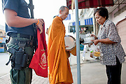 """Sept. 25, 2009 -- PATTANI, THAILAND: Soldiers and police officers accompany Buddhist monks on their morning rounds soliciting alms in Pattani, Thailand. Monks have been the targets of Muslim insurgent assassins who kill representatives of Thai Buddhist culture include monks and teachers. Thailand's three southern most provinces; Yala, Pattani and Narathiwat are often called """"restive"""" and a decades long Muslim insurgency has gained traction recently. Nearly 4,000 people have been killed since 2004. The three southern provinces are under emergency control and there are more than 60,000 Thai military, police and paramilitary militia forces trying to keep the peace battling insurgents who favor car bombs and assassination.  Photo by Jack Kurtz / ZUMA Press"""