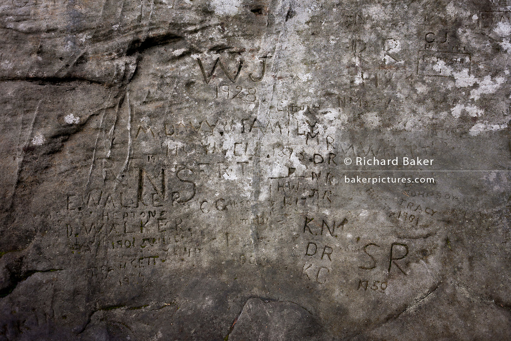 The names from a century of visitors carved on a rocky outcrop, remaining as graffiti on natural stone, on 25th September 2017, in Rothbury, Northumberland, England.