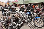 Leather clad bikers ride down Main Street past a customized Harley-Davidson chopper during the 74th Annual Daytona Bike Week March 7, 2015 in Daytona Beach, Florida.