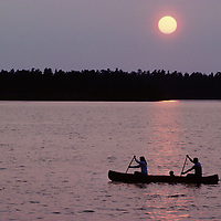 A family canoes on Lake of the Woods in Ontario, Canada during a smoky sunset.