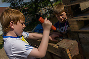 Boys use claw hammer in risk averse playground called The Land on Plas Madoc Estate, Ruabon, Wrexham, Wales.
