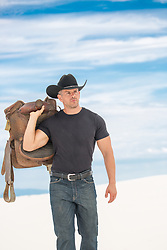 hot cowboy carrying a saddle over his shoulder